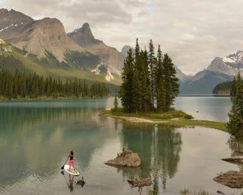 Woman standup paddle boarding on a large alpine lake