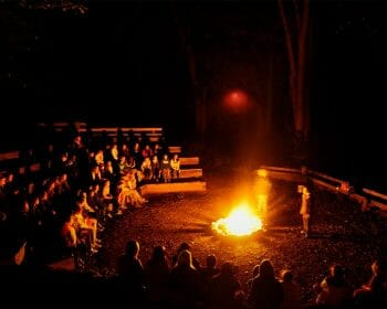 Campfire surrounded by lots of people sitting in stadium style seating