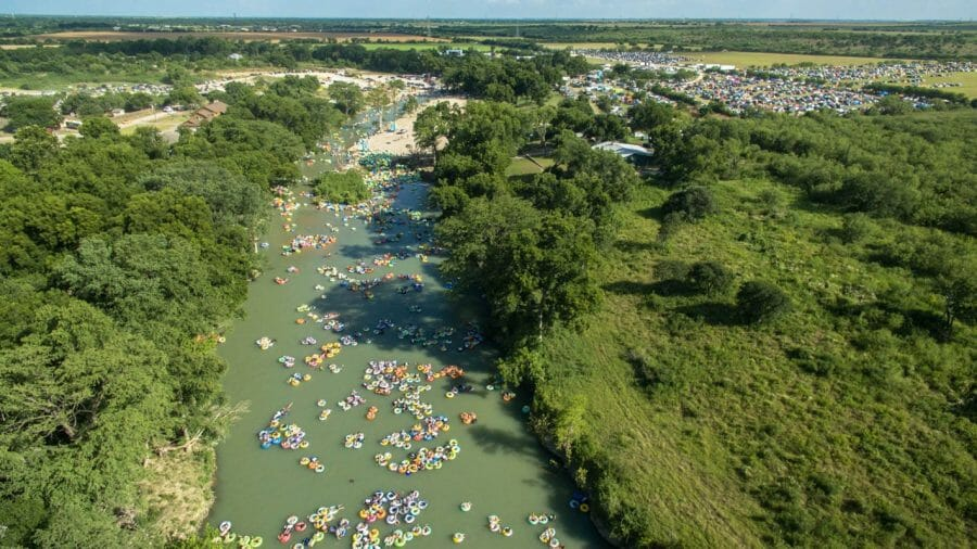 Drone shot of hundreds of rafters floating down a river.
