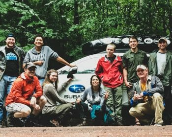 A group of people posing in front of a Subaru outback car