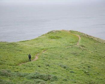 Lone hiker walking along trail in remote setting