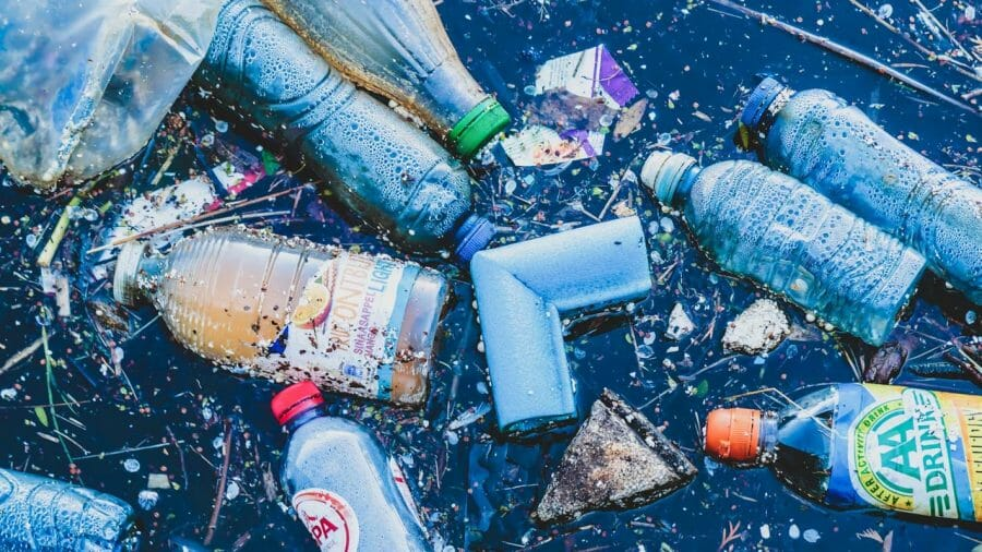 Various plastics floating on body of water.