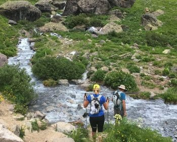 Two hikers preparing to cross a river.