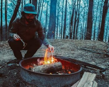 Man stoking a fire while camping