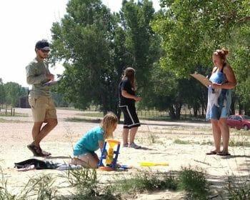 Volunteers taking notes in a sandy field