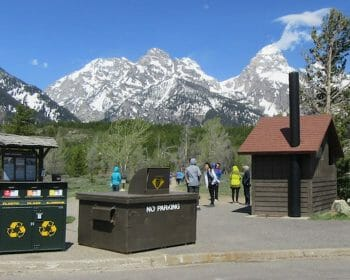 Trash cans at a trailhead with the backdrop of snow-capped mountains