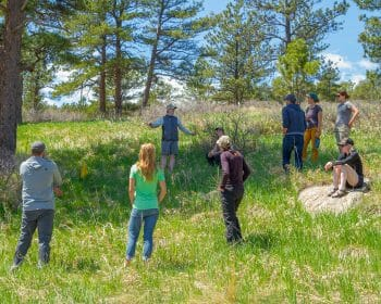 Leave No Trace trainer providing instruction to group of students in an open field