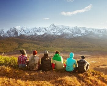 Group of young adults sitting and admiring mountains