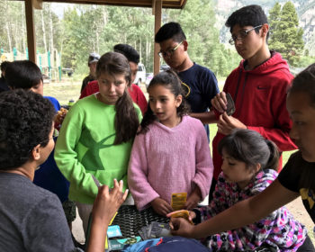 Group of children listening to someone speaking.