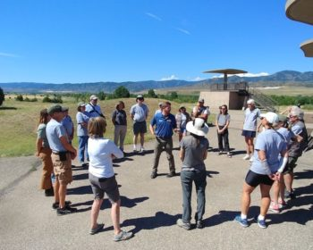 Leave No Trace trainer talking to group of onlookers in outdoor setting
