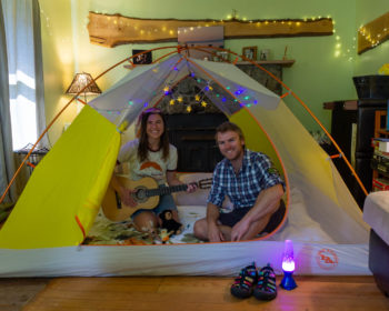 Two leave no trace traveling trainers posing in their tent in their living room.