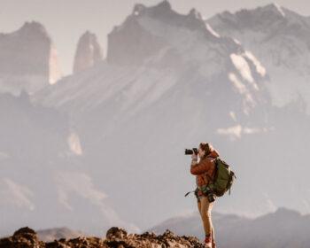 Photographer looking through lens of camera in mountainous backcountry area