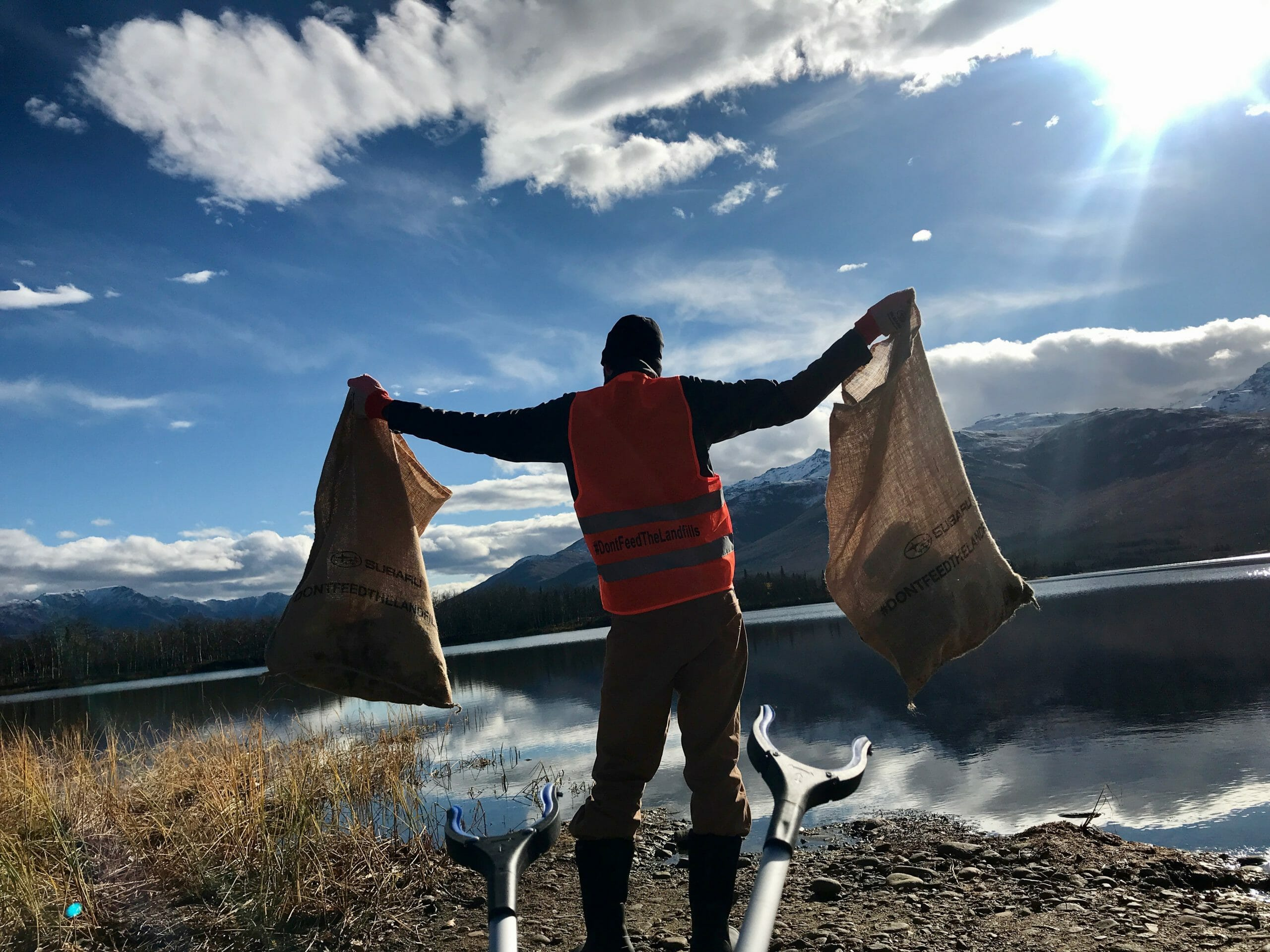 Back of man holding up two bags of trash on the shores of a lake surrounded by mountains