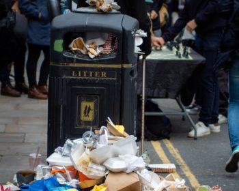 Overflowing trash can in a city